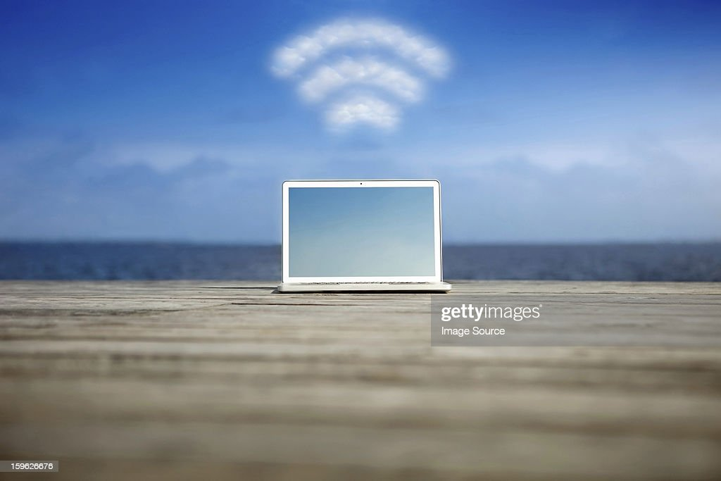 Laptop with wifi symbol at the coast : Stock Photo