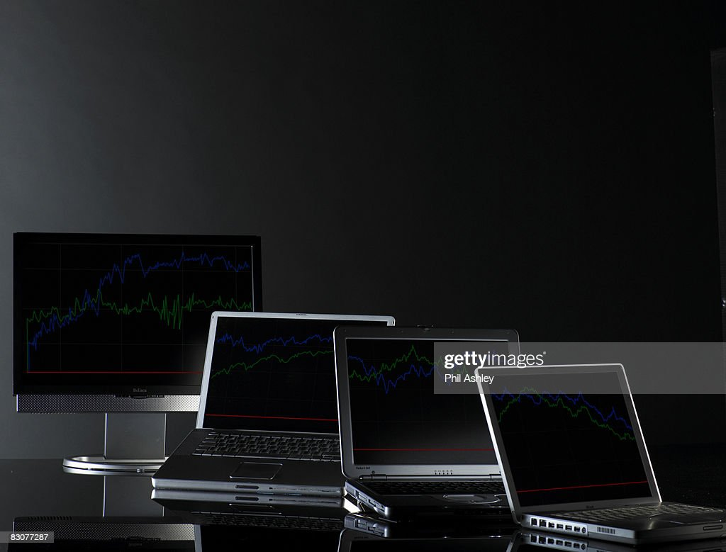 laptops with financial data on screens : Stock Photo