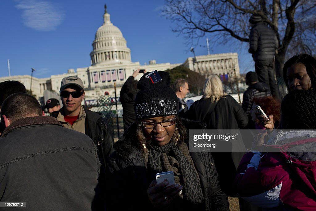 Laquanda Pierce, of Miami, Florida, wears an Obama hat as she checks her Apple Inc. iPhone while standing in front of the Capitol building ahead of the presidential inauguration in Washington, D.C., U.S., on Sunday, Jan. 20, 2013. As he enters his second term U.S. President Barack Obama has shed the aura of a hopeful consensus builder determined to break partisan gridlock and adopted a more confrontational stance with Republicans. Photographer: Victor J. Blue/Bloomberg via Getty Images