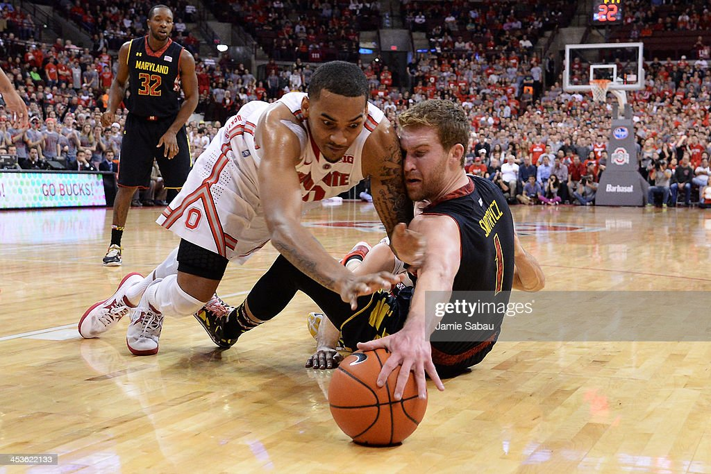 LaQuinton Ross #10 of the Ohio State Buckeyes and Evan Smotrycz #1 of the Maryland Terrapins battle for control of a loose ball in the first half on December 4, 2013 at Value City Arena in Columbus, Ohio. Ohio State defeated Maryland 76-60.