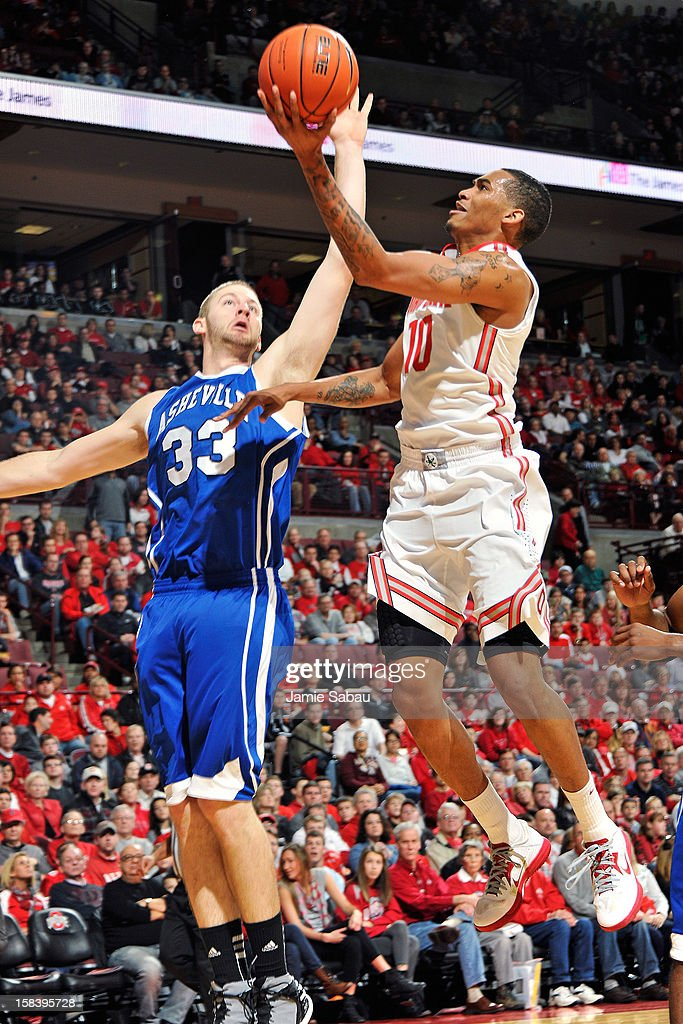 LaQuinton Ross of the Ohio State Buckeyes attempts a layup as DJ Cunningham of the UNC Asheville Bulldogs defends in the first half on December 15...