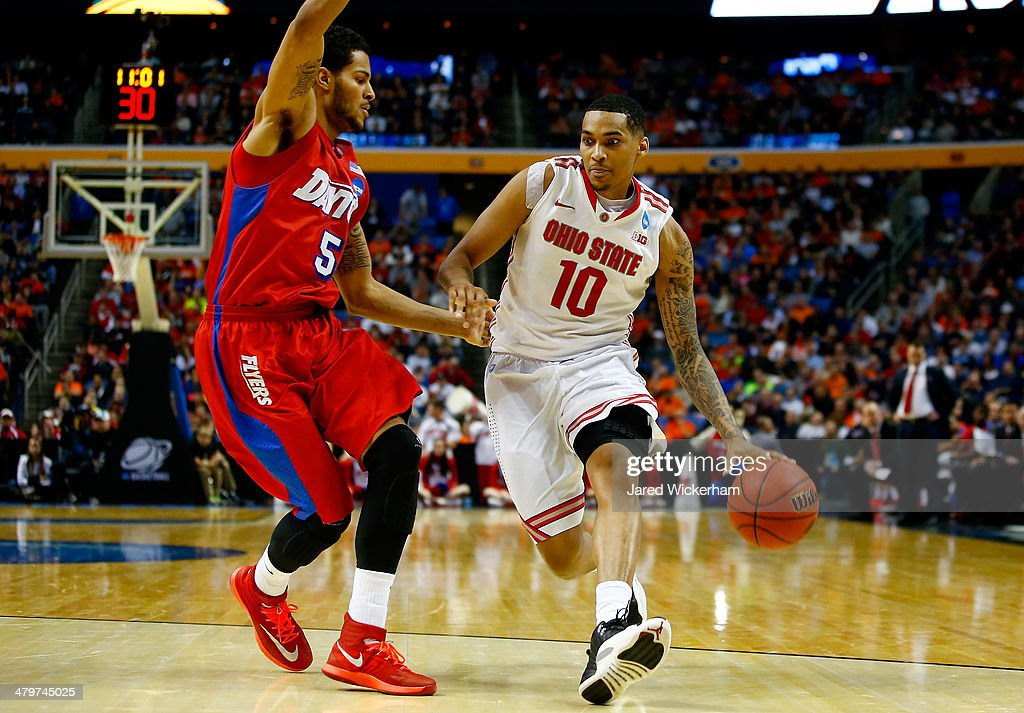 LaQuinton Ross of the Ohio State Buckeyes drives to the basket as Devin Oliver of the Dayton Flyers defends during the second round of the 2014 NCAA...