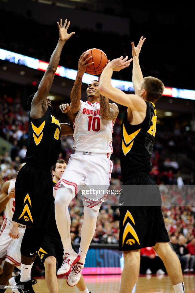 LaQuinton Ross of the Ohio State Buckeyes goes up for a layup while being defended by Jarrod Uthoff of the Iowa Hawkeyes and Gabriel Olaseni of the...