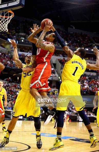 LaQuinton Ross of the Ohio State Buckeyes is defended by Jordan Morgan and Glenn Robinson III of the Michigan Wolverines during the second half of...