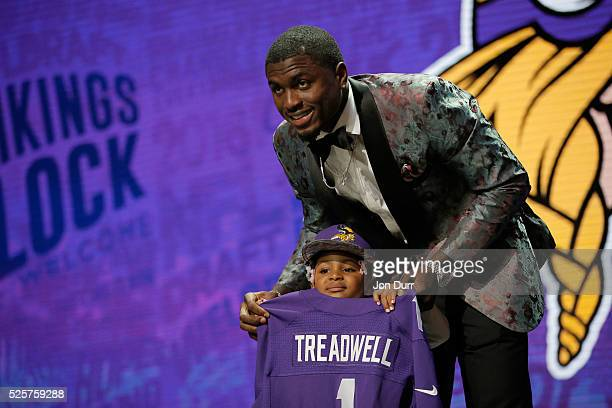 Laquon Treadwell of Ole Miss holds up a jersey with his daughter Madison after being picked overall by the Minnesota Vikings during the first round...