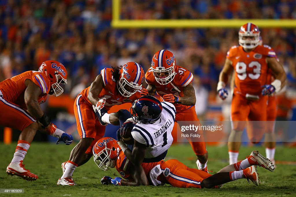 Laquon Treadwell of the Mississippi Rebels is stopped by Daniel McMillian and Jalen Tabor of the Florida Gators during the first half of the game on...