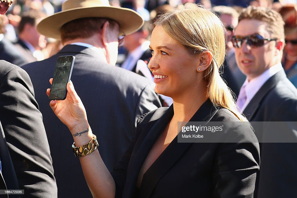Lara Bingle shows her friend something on her iPhone on Australian Derby Day at Royal Randwick Racecourse on April 13, 2013 in Sydney, Australia.