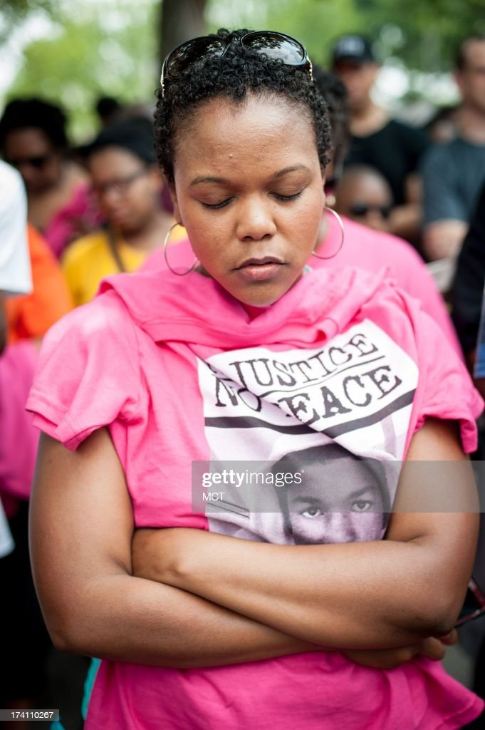 Larc Pickett, 27, of Woodbridge, Virginia, bows her head in prayer at the start of the 'Justice for Trayvon' rally at the E. Barrett Prettyman Federal Courthous in Washington, D.C., Saturday, July 20, 2013. 'I think we all understand the injustice,' she said. 'This is a reminder of what we have to fight for and this is why I've come down; to fight for the future of my children and all children as well.'