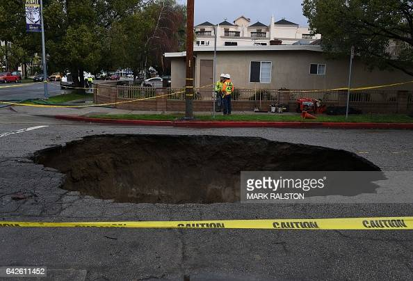 A large 20footdeep sinkhole that swallowed two vehicles in North Laurel Canyon Blvd in Los Angeles is cordonedoff on February 18 after a powerful...