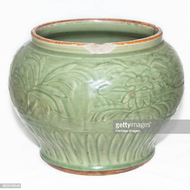 A large and heavilypotted celadon jar It is carved with a wide band of peonies above a petal band encircling the base There is a big crack on one...