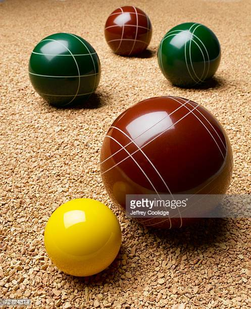 Large balls and small yellow ball on gravel, close up