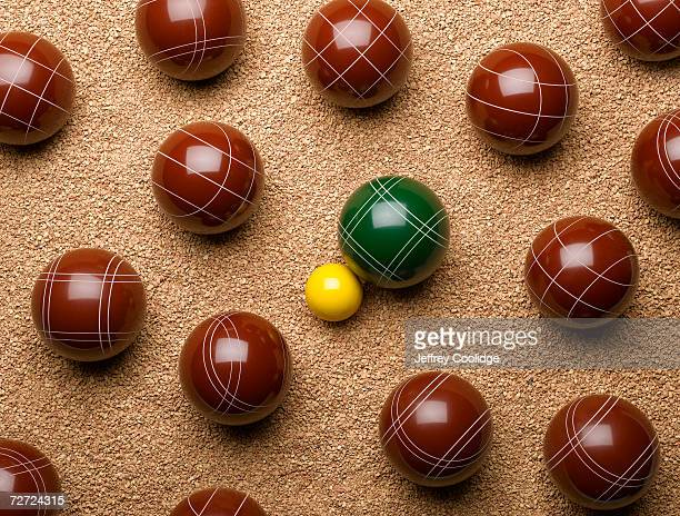 Large balls on gravel with one small yellow ball in centre, overhead view
