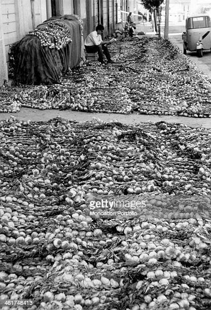 A large batch of garlic lays to dry along the street while on the background a man sits while reading the newspaper next to an Apecar parked by the...