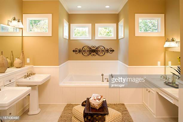 Large bathroom with pedestal sinks and large tub