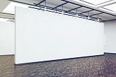 Side veiw of a large blank white wall in an art gallery. Dark wood floor. Concept of exhibition. 3d rendering. Mock up. Toned image