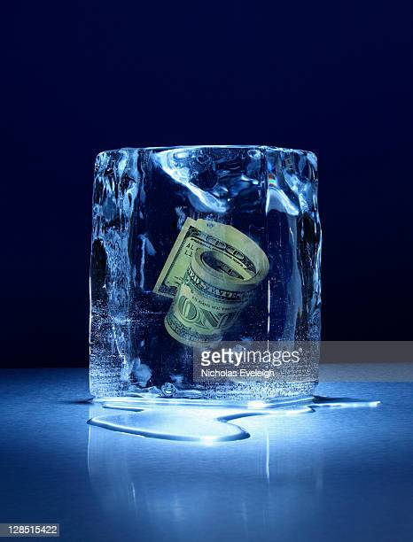 Large block of ice with roll of money frozen inside