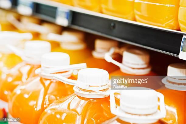 Large bottles of orange juice in supermarket fridge