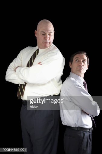 Large businessman standing back to back with small businessman : Stock Photo