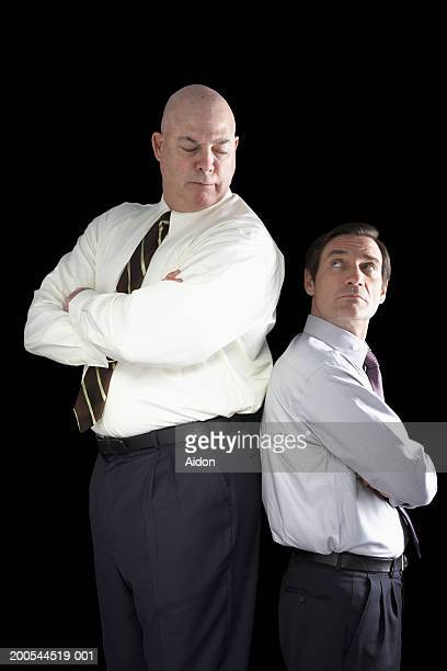 Large businessman standing back to back with small businessman