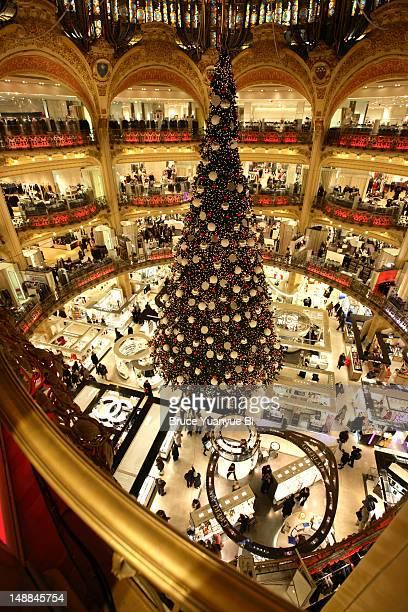 Large Christmas tree decorating Galeries Lafayette store floor.