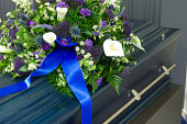 A blue coffin in a morgue with a flower arrangement