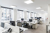 Desks and chairs in an empty office with telephones and office equipment, modern square lighting on white ceiling