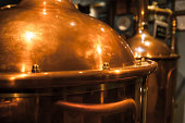 Large, copper container for brewing, many reflections of light.