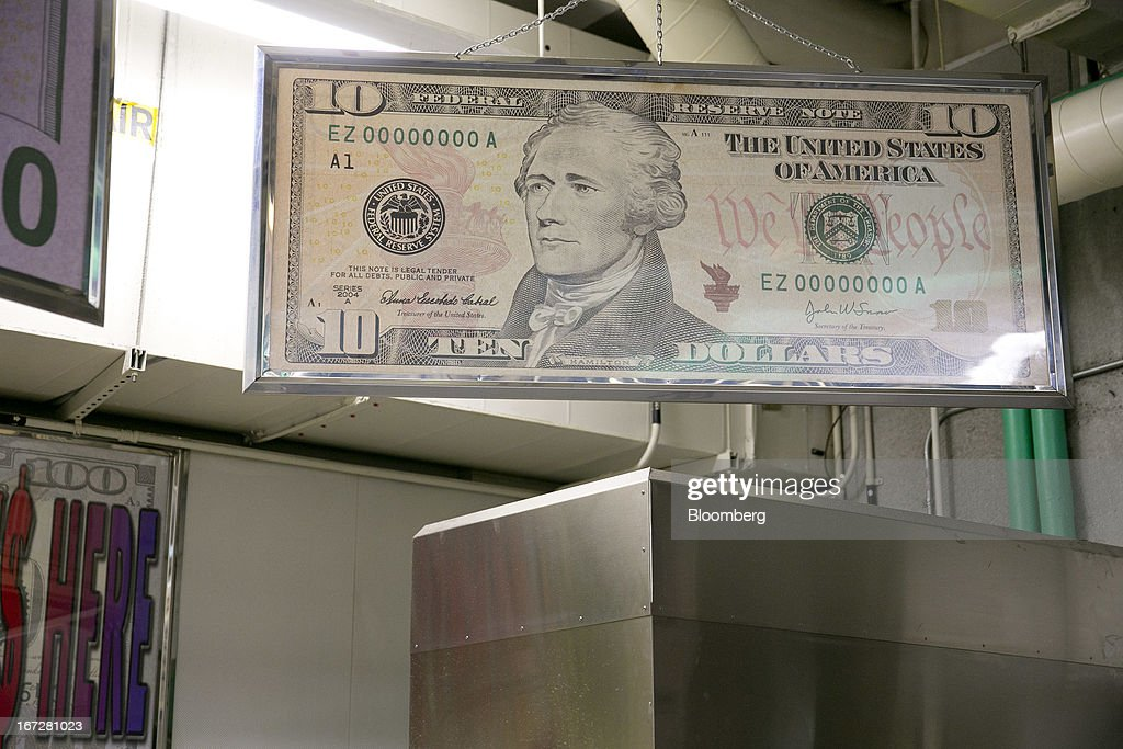 A large copy of a ten dollar note hangs inside the Bureau of Engraving and Printing in Washington, D.C., U.S., on Tuesday, April 23, 2013. Stocks rallied amid growth in U.S. home sales, better-than-forecast earnings and speculation the European Central Bank will cut interest rates. U.S. equities recovered after briefly erasing gains following a false report of explosions at the White House. Photographer: Andrew Harrer/Bloomberg via Getty Images