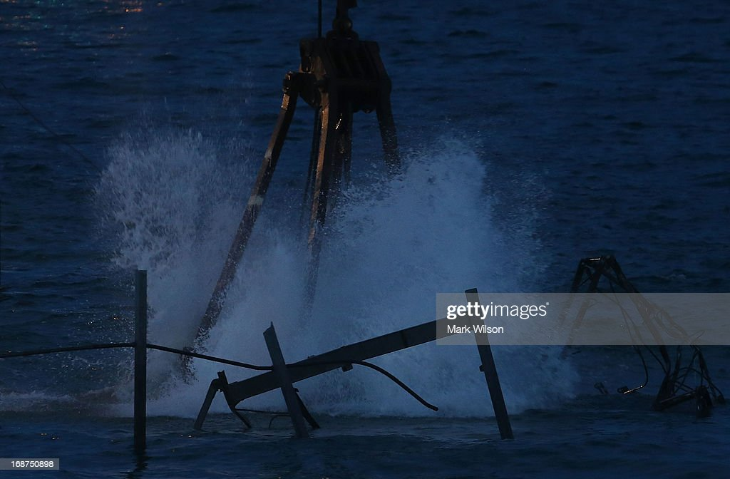 A large crane picks up the remaining pieces of Jet Star roller coaster that has been in the ocean for six months after the Casino Pier is sat on collapsed when Superstorm Sandy hit, May 14, 2013 in Seaside Heights, New Jersey. The Casino Pier has contracted Weeks Marine to remove the Jet Star roller coaster from the Atlantic Ocean.