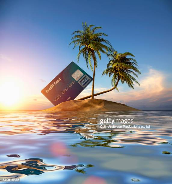 Large credit card beached on tropical island