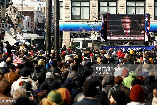 A large crowd celebrates while watching the inauguration of Barack Obama as the 44th president of the United States on a large screen in the...