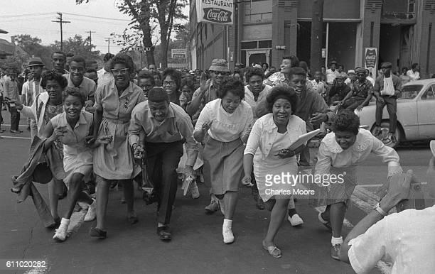 A large crowd crouch down snap their fingers and cross a street Birmingham Alabama 1963