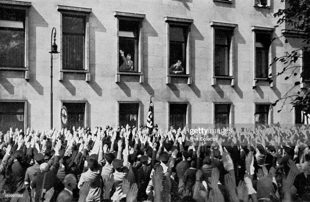 Large crowd from the Saargebiet in front of the chancellery Berlin Germany 1936 Nazi Chancellor Adolf Hitler returns the crowd's salute from a window...