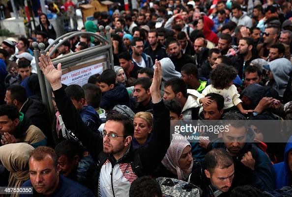 A large crowd of migrants wait for authorities to allow them to board a train leaving for the Austrian border at the Keleti railway station on...