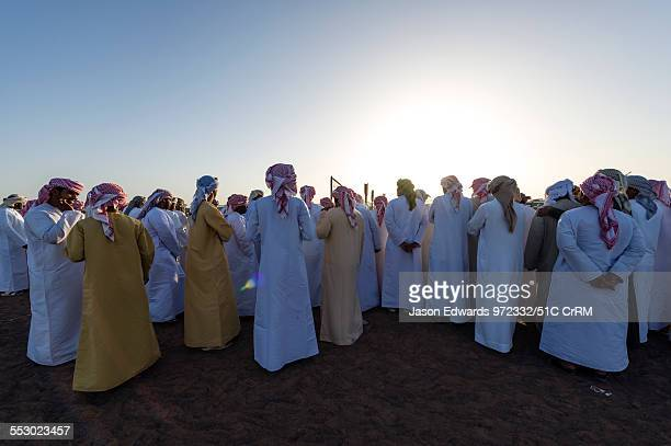A large crowd of Muslim men wearing dishdasha and masar gather to watch camel races Bidiya Sharqiya Region Sultanate of Oman