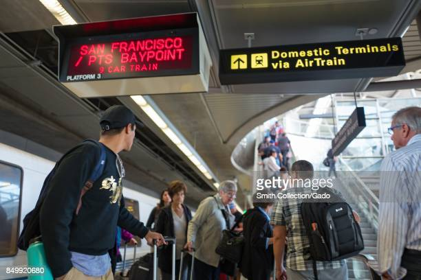 A large crowd of passengers exits a Bay Area Rapid Transit train at San Francisco International Airport and takes an escalator towards the airport...