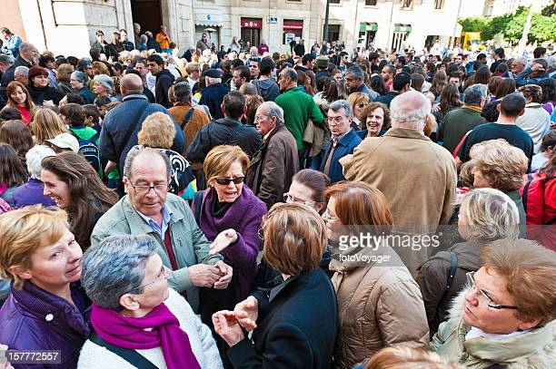 Large crowd of people all ages in street Spain