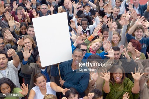 Large Crowd of People with Their Hands Raised in the Air with One Man Holding a Blank Placard