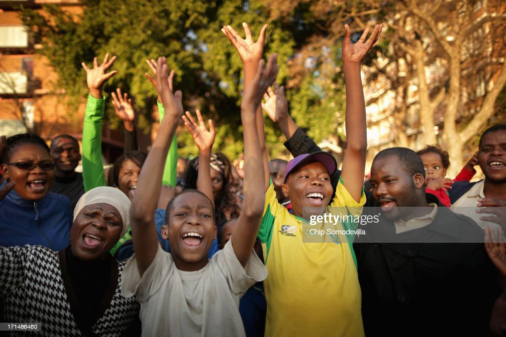 A large crowd of supporters cheer after singing the South African national anthem outside of the Mediclinic Heart Hospital where former South African President Nelson Mandela is being treated June 25, 2013 in Pretoria, South Africa. South African President Jacob Zuma confirmed on June 23 that Mandela's condition has become critical since he was admitted to the hospital over two weeks ago for a recurring lung infection.