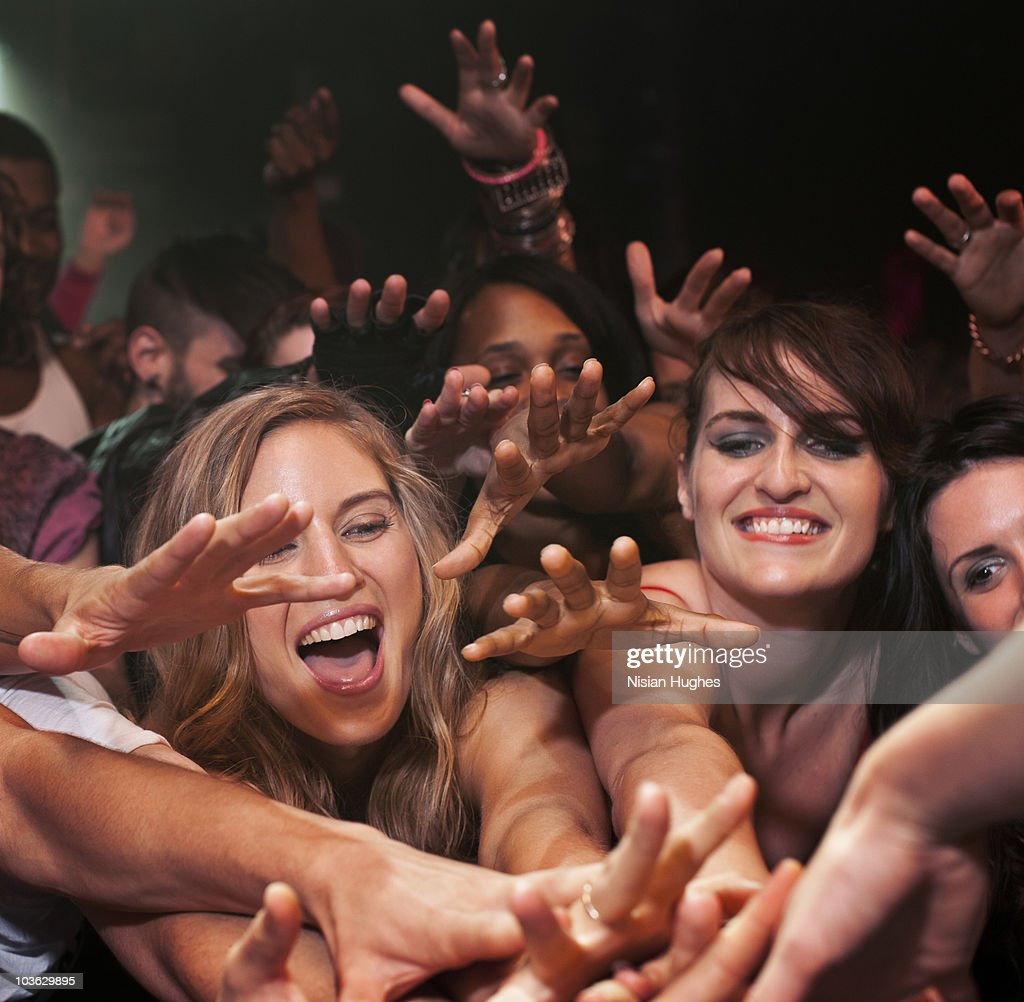 Large crowd reaching for a hand : Stock Photo