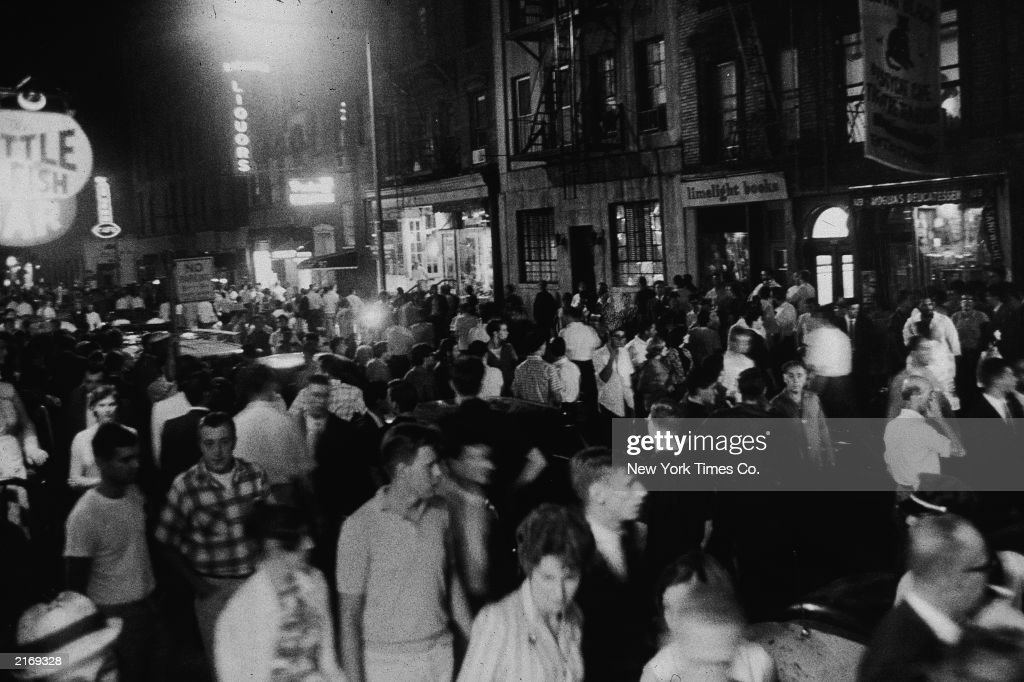 A large crowd stands outdoors in the street after the police investigated a brawl Greenwich Village New York City August 2 1963