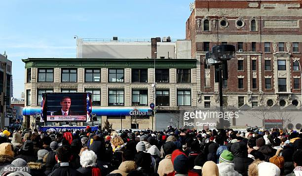 A large crowd watches the inauguration of Barack Obama as the 44th president of the United States on a large screen in the neighborhood of Harlem...