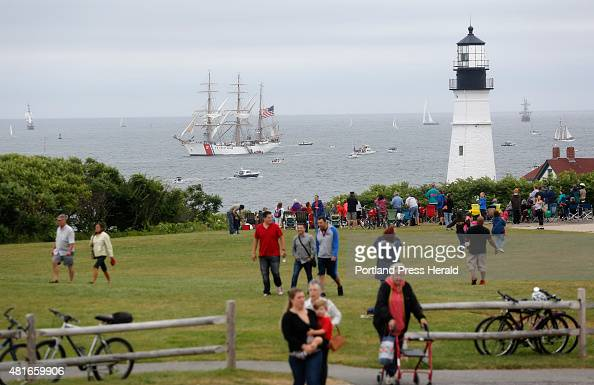 Large crowds gather to watch the Tall Ships Portland 2015 parade from Fort Williams Park The Eagle passes Portland Head Light as park visitors search...