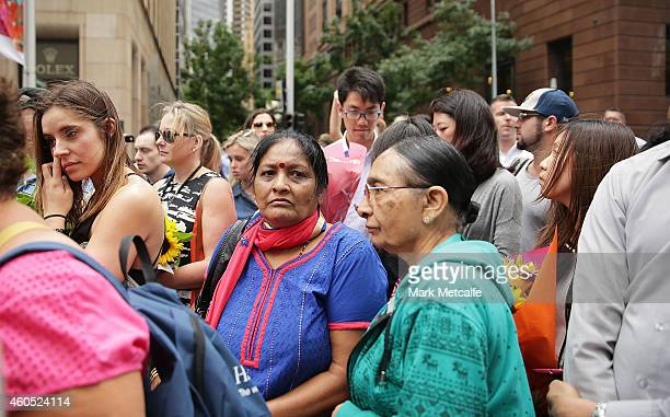 Large crowds wait in line to lay dwon flowers in Martin Place on December 16 2014 in Sydney Australia Sydney siege gunman Man Haron Monis was shot...