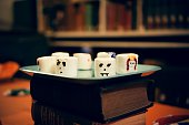 Large decorated marshmallows sitting on a place that is sitting on top of a stack of books Halloween at Johns Hopkins University's George Peabody...