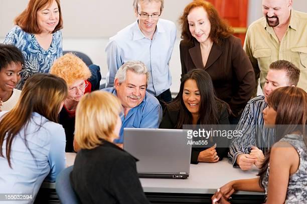 Grand groupe de différents en face d'un ordinateur portable