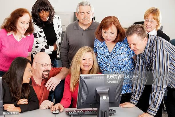 Grand groupe de différents en face de l'ordinateur