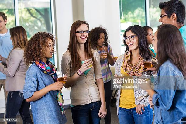 Large diverse group of college freshmen meeting during orientation party