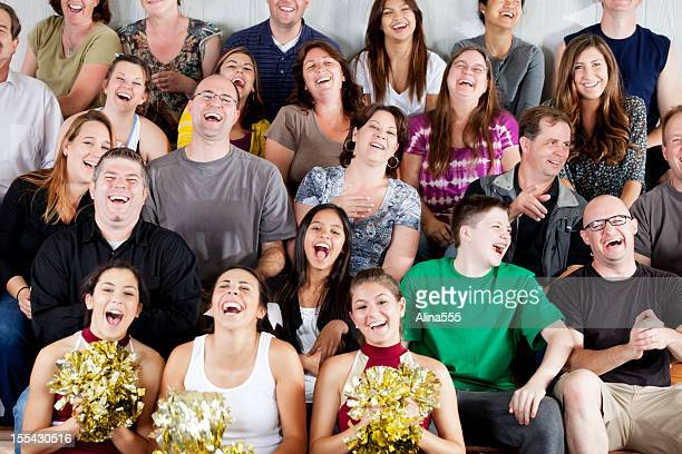Large diverse group of people laughing at the game