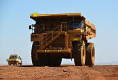 A small light vehicle drives past a large haul truck on a minesite.